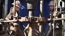 """In this Feb. 21, 2012, file photo, oil field workers drill into the Gypsum Hills near Medicine Lodge, Kan., using horizontal drilling and a technique known as hydraulic fracturing, or """"fracking,"""" to coax out oil and gas. (Orlin Wagner/The Associated Press)"""