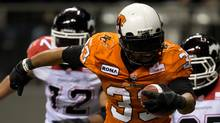 B.C. Lions' Andrew Harris, centre, rushes past Calgary Stampeders' Juwan Simpson, left, and Keon Raymond for a touchdown during the second half of a CFL football game in Vancouver, B.C., on Saturday October 6, 2012 (The Canadian Press)