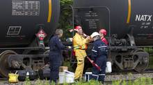 People from several juristictions including the Ministry of the Environment for Canada and Quebec, and the RCMP prepare to do some investigative work in the area of the nine remaining tank cars sitting on the tracks in Nantes, PQ on July 11, 2013. This is where the ill-fated train that derailed in Lac-Mégantic originated from early Saturday morning. (Peter Power/The Globe and Mail)
