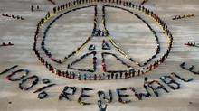 """People make the """"Pray for Paris"""" sign along with the slogan """"100 percent renewable"""" in Paris on December 6, 2015 on the sidelines of the COP21 climate change conference. / (MARTIN BUREAU/AFP/Getty Images)"""