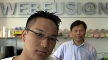 Ryan Cha, shown in June 2003 with his father Yoon Chui, co-owners of the Webfusion Internet cafe in Toronto are located. (Fred Lum/The Globe and Mail)