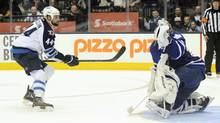 Winnipeg Jets Zach Bogosian (L) scores on Toronto Maple Leafs goalie Ben Scrivens during a shoot out during their NHL game in Toronto March 16, 2013. (AARON HARRIS/REUTERS)