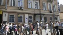 "Clients of the ""Neva"" tourism company stand in a line to get into its office while attempting to get back their money for paid vacation packages after the announcement of the bankruptcy of the company in St. Petersburg on July 16, 2014. Low-cost carrier Dobrolyot, operated by Aeroflot, suspended all flights last week after its airline leasing agreement was cancelled under European Union sanctions because it flies to Crimea, a region Russia annexed from Ukraine in March. (STRINGER/REUTERS)"