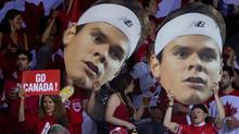 Canadian fans hold up oversized photographs of Canada's Milos Raonic (DARRYL DYCK/The Canadian Press)