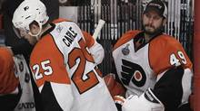 Philadelphia Flyers goalie Michael Leighton (49) sits on the bench as Flyers defenseman Matt Carle (25) comes off after a shift against the Chicago Blackhawks in the second period of Game 5 of the NHL Stanley Cup hockey finals on Sunday, June 6, 2010, in Chicago. Leighton was pulled for goalie Brian Boucher. (AP Photo/Charles Rex Arbogast) (Charles Rex Arbogast)