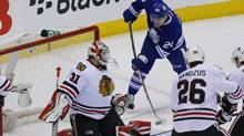 Toronto, Ontario, CAN; Toronto Maple Leafs forward Peter Holland (24) scores on Chicago Blackhawks goaltender Antti Raanta (31) as forward Michal Handzus (26) looks on during the first period at the Air Canada Centre. (USA Today Sports)