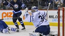 In this file photo, Winnipeg Jets' Zach Redmond (L) celebrates his goal against the Toronto Maple Leafs during the second period of their NHL hockey game in Winnipeg February 7, 2013. The Jets announced on Saturday they have signed Redmond to a one-year contract. (FRED GREENSLADE/REUTERS)