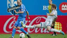 Montreal Impact's Justin Mapp, left, and Vancouver Whitecaps' Jordan Harvey battle for the ball during first half MLS action in Montreal, Saturday, September 21, 2013. (Graham Hughes/THE CANADIAN PRESS)
