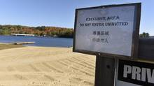 A sign written in english and Chinese is posted beside a private property sign by the beach belonging to Blue Spruce Resort, on Oct. 12, 2016. (Fred Lum/The Globe and Mail)