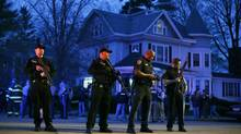 Police officers guard the entrance to Franklin Street where there is an active crime scene search for suspect in the Boston Marathon bombings, Friday, April 19, 2013, in Watertown, Mass. (Matt Rourke/AP)