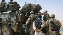 Canadian soldiers escort a detainee in Afghanistan. (Les Perreaux/The Globe and Mail)