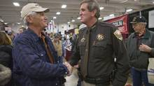 Sheriff John Cooke, right, who opposes stricter gun laws, shakes hands with an attendee at the Colorado Farm Show in Greeley, Colo. Rural sheriffs across the country have reacted in public opposition to President Barack Obama's call for stiffer gun laws, releasing a deluge of letters, position papers and statements laying out their arguments in stark terms. (MATTHEW STAVER/NYT)