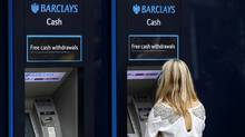 A customer uses a Barclays ATM in central London, July 23, 2010. (ANDREW WINNING/ANDREW WINNING/REUTERS)