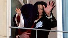 Pop star Michael Jackson (R) carries one of his children, with a cloth over draped his head, as they wave to wellwishers on the balcony of a suite in Berlin's Hotel Adlon 20 November 2002. (TOM MAELSA/AFP)