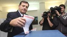 Serb Prime Minister Milorad Dodik of the Union of Independent Social Democrats (SNSD) casts his vote at polling station in Banja Luka, Bosnia,120 km west of Sarajevo, on Sunday, Oct. 3, 2010. With the top candidates fiercely at odds over Bosnia's future, voters cast ballots Sunday in elections likely to further entrench their nation's ethnic divisions and threaten possible EU entry. (Amel Emric/AP Photo/Amel Emric)