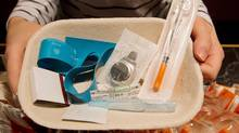 Registered nurse Sammy Mullally holds a tray of supplies to be used by a drug addict at the Insite safe injection clinic in Vancouver on May 11, 2011. (DARRYL DYCK/THE CANADIAN PRESS)