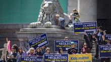Amadeus Sars, 5, plays with his sister Ella Sars, 7, at the Vancouver Art Gallery while their father, a concerned parent, takes part in a noon rally to support striking B.C. teachers on Monday. (John Lehmann/The Globe and Mail)