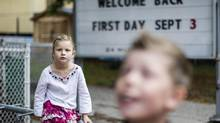 Nine year old Charles and six year old Juliette Mercule wait outside a Toronto school as they prepare for the first day back in school. (Chris Young/Chris Young for The Globe and Mail)