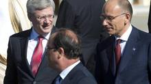 Canadian Prime Minister Stephen Harper speaks briefly with French President Francois Hollande and Italian Prime Minister Enrico Letta, right, following the G20 leader family photo at the G20 Summit Friday September 6, 2013 in St. Petersburg, Russia. (Adrian Wyld/THE CANADIAN PRESS)