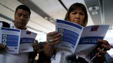 People read zika virus flyers from an information campaign by the Chilean Health Ministry at the departures area of Santiago's international airport, Chile January 28, 2016. (IVAN ALVARADO/REUTERS)