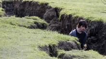 A man walks in a large earthquake crack in the ground in Kaiapoi near Christchurch, New Zealand, Thursday, Sept. 9, 2010. (Rob Griffith/ The Associated Press/Rob Griffith/ The Associated Press)