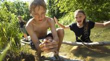 Colm Beattie, 12,and his younger sister Avery, spend some time swimming in the pond and looking for frogs in the creek at the back of their family's property in Collingwood, Ont., after getting home from their last school day of the year Thursday. Mom, Leslie McIntyre, behind, wants to keep her childrens' summer unstructured, and will allow them to play and explore rather than putting them in organized camps. (Peter Power/The Globe and Mail)
