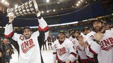 University of New Brunswick Varsity Reds forward Colby Pridham hoists the University Cup trophy after defeating the Saint Mary's Huskies at the 2013 CIS University Cup hockey final in Saskatoon on March 17, 2013. (Liam Richards/THE CANADIAN PRESS)