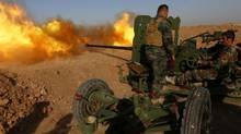 Iraqi Kurdish Peshmerga fighters fire an anti-tank cannon on the front line near Hasan Sham village, Iraq, on May 29, 2016. (SAFIN HAMED/AFP/Getty Images)