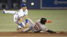 Toronto Blue Jays second baseman Munenori Kawasaki (66) tags out Baltimore Orioles right fielder Nick Markakis (21) during the sixth inning at Rogers Centre, Tuesday, August 5, 2014. (Nick Turchiaro/USA Today Sports)