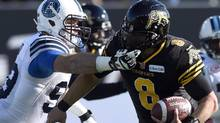 Daryl Waud of the Toronto Argonauts reaches for the mask of the Hamilton Tiger-Cats' Jeremiah Masoli for a major foul during a CFL game on Nov. 15, 2015. (Frank Gunn/THE CANADIAN PRESS)