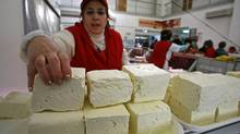 A woman arranges a piece of traditional Romanian cheese at Obor market in Bucharest. The Canadian government is preparing to raise its protectionist drawbridge and admit more European cheese into this country in return for greater access to EU markets for Canada's beef and pork. (BOGDAN CRISTEL/REUTERS)