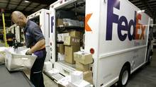 A FedEx employee loads packages into his truck at the FedEx express station in Nashville, Tenn. (Mark Humphrey/AP)