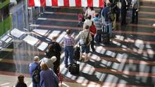 Long lines of people wait to enter the security checkpoint before boarding their aircraft at Reagan National Airport in Washington, April 25, 2013. U.S. airlines have partly blamed poor quarterly results on FAA-imposed furloughs for air traffic controllers. (LARRY DOWNING/REUTERS)