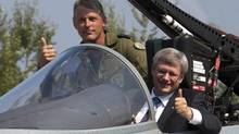 Prime Minister Stephen Harper sits in a CF-18 Hornet as Major Daniel Dionne explains the controls at the L-3 plant in Mirabel, Que., on Sept. 1, 2010. (Ryan Remiorz/The Canadian Press)