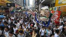 Protesters hold an effigy of Hong Kong Chief Executive Leung Chun-ying as they march during an annual protest in downtown Hong Kong Tuesday, July 1, 2014. (Kin Cheung/AP)