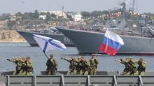 Russian servicemen rehearse Friday for their Navy Day parade on Sunday in the Crimean port of Sevastopol. (STRINGER/REUTERS)