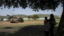 Children look at an Israeli army mobile artillery unit in this file photo. (BAZ RATNER/REUTERS)