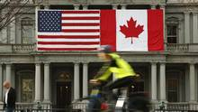 A cyclist passes U.S. and Canadian flags placed side-by-side on the Eisenhower Executive Office Building next to the White House in Washington. (KEVIN LAMARQUE/REUTERS)