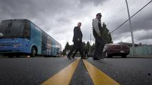 NDP Leader John Horgan, left, crosses a road in Surrey, B.C. on his way to a campaign stop on Wednesday. Partisan campaign rhetoric has increased in recent days ahead of the May 9 provincial election. (DARRYL DYCK/THE CANADIAN PRESS)