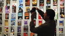 "A man takes photographs beside a display of James Bond books on display at the ""For Your Eyes Only, Ian Fleming and James Bond"" exhibition at the Imperial War Museum in London, Wednesday April 16, 2008. (MATT DUNHAM/AP)"