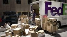 A FedEx worker looks over his packages on a New York street on Tuesday, May 29, 2007. (MARK LENNIHAN/AP)