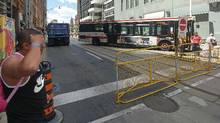 A TTC bus and city dump truck block the intersection at Yonge Street and Queen Street west during Canada 150 celebrations in nearby Nathan Phillips Square. Toronto police spokesperson Mark Pugash confirms the vehicles were placed here to prevent any possible attack on the thousands of people that gathered near here during the long weekend. (Kenny Sharpe/The Globe and Mail)