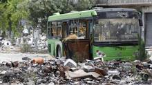 A wrecked bus is seen on a damaged street filled with debris in the old city of Aleppo on June 19, 2013. (MUZAFFAR SALMAN/REUTERS)