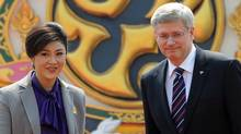 Prime Minister Stephen Harper is escorted by his Thai counterpart, Yingluck Shinawatra, as he visits Government House in Bangkok on March 23, 2012. (Sean Kilpatrick/The Canadian Press/Sean Kilpatrick/The Canadian Press)