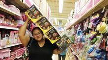 "Bianca Lopez balances toys on her head at a Toys ""R"" Us outlet in Corpus Christi, Texas. (RACHEL DENNY CHOW/AP/RACHEL DENNY CHOW/AP)"