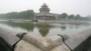 A man looks at the moat of the Forbidden City shrouded in haze in Beijing July 28, 2008.