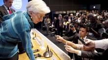 International Monetary Fund (IMF) Managing Director Christine Lagarde (L) talks to members of the media after her news conference at the annual meetings of the IMF and the World Bank Group in Tokyo October 11, 2012. (REUTERS)