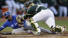 Oakland Athletics catcher Stephen Vogt, right, tags out Toronto Blue Jays' Ryan Goins at home plate in the third inning of a baseball game Tuesday, June 6, 2017, in Oakland, Calif. (Ben Margot/AP)