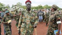 Lord's Resistance Army commander Caesar Achellam, centre, is escorted by members of the Ugandan army on arrival at the army operation base in Nera in South Sudan May 13, 2012 after he was captured by Ugandan soldiers. (James Akena/Reuters/James Akena/Reuters)