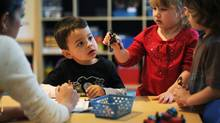 Teacher Nicole Abdool, left, works with students from left, Michael Fialho, 3, Alexis Gimnidis, 3, and Connor Cacoutis, 4, during a FasTracKids early learning program class in Thornhill, Ont. (Kevin Van Paassen/Kevin Van Paassen/The Globe and)